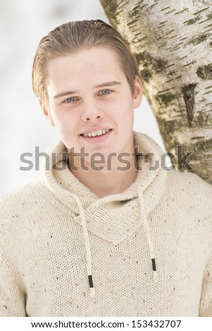 Christmas scene with natural looking teenage male outdoors in snow covered winter landscape. - stock photo