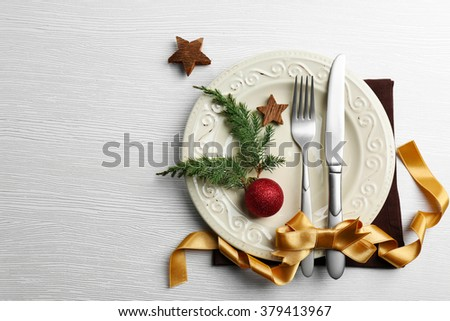 Christmas serving cutlery on plate over light wooden table - stock photo