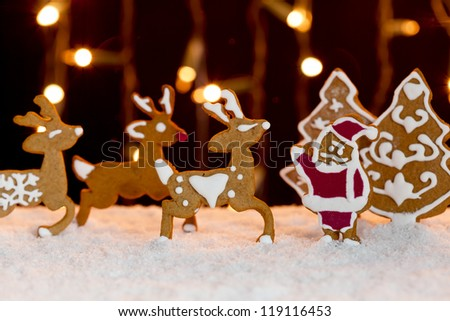 Christmas setting in warm lights - gingerbread deers and santa standing in snow - stock photo