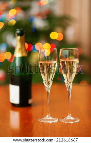 Christmas setting with bottle of champagne and Christmas tree in the background - stock photo