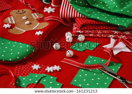 Christmas sewing still life includes fabric and craft supplies for creating festive decorations and ornaments.  Handmade stocking with appliqued gingerbread man in background. - stock photo