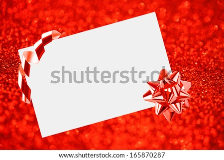 Christmas sheet of paper with bow on red defocused background - stock photo