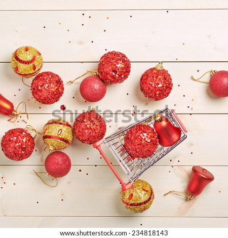 Christmas shopping background composition of a multiple decoration balls and tiny shopping cart over the wooden surface - stock photo