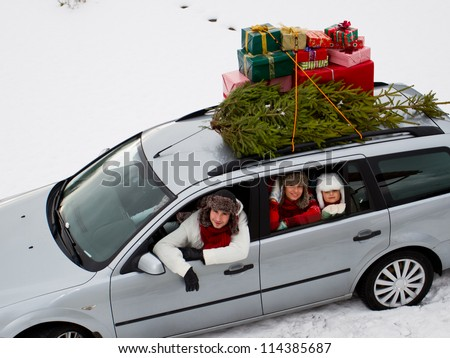 Christmas shopping, celebrating - the family is riding a car with christmas tree and gifts on the roof of the car - stock photo
