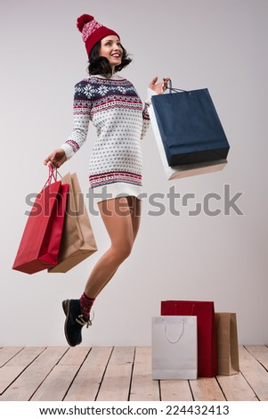 Christmas shopping. Pretty woman jumping with shopping bags against white wall background, wearing knitted hat and dress - stock photo
