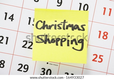 Christmas Shopping reminder written on a yellow paper adhesive note stuck to a wall calendar background - stock photo