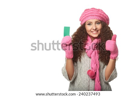 Christmas shopping. Smiling beautiful woman in winter red hat and scarf showing blank credit card, over white background - stock photo