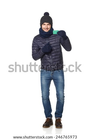 Christmas shopping. Smiling young man in winter hat and scarf showing blank credit card, over white background - stock photo