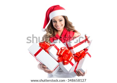 Christmas shopping woman holding many Christmas gifts in her arms wearing santa hat.  - stock photo