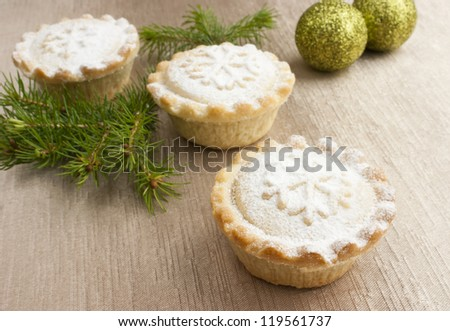 Christmas short crust pastry mince pies dusted with icing sugar on golden background with Christmas ornaments and a twig of a pine tree. - stock photo
