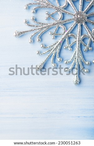 Christmas silver snowflake on light blue wood background with space for text. Merry christmas card. Winter holidays. Xmas theme. - stock photo