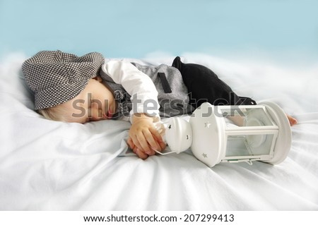Christmas sleeping newborn baby with lantern in suit and hat on blue background. Photo for calendar, card  etc. Christmas concept. - stock photo