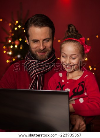 Christmas - smiling father and daughter playing game on laptop computer. Happy family time - modern lifestyle. Christmas tree with lights on dark red as background. - stock photo