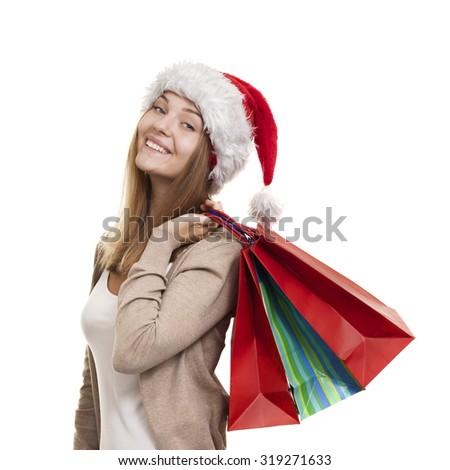 Christmas smiling girl, young woman in santa hat with shopping bags in bright - stock photo