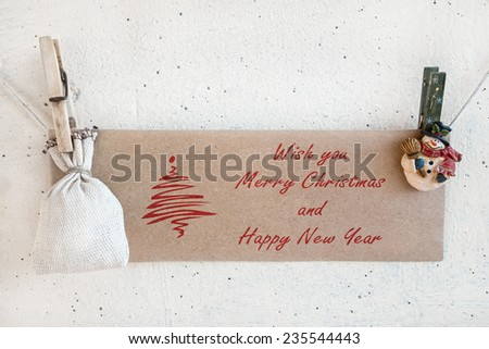 Christmas snowman clothespins hanging on clothesline or rope and holding brown Christmas greeting card and sack on plaster background - stock photo