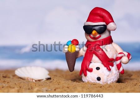 Christmas snowman on beach while vacation - stock photo