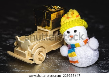 Christmas snowman toy and old vintage wooden automobile with golden or yellow gift box on silver or metal grunge surface - stock photo