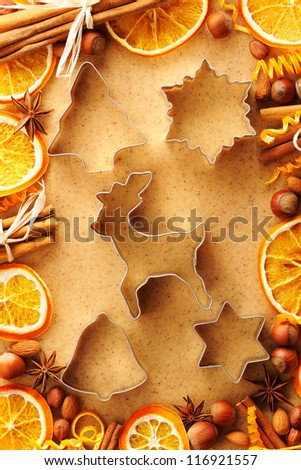 Christmas spices and cookie cutters over homemade gingerbread dough - stock photo