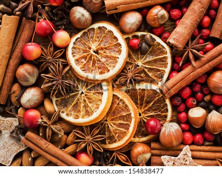 Christmas spices, fruits, nuts and berries on the wooden background. Shallow dof. - stock photo