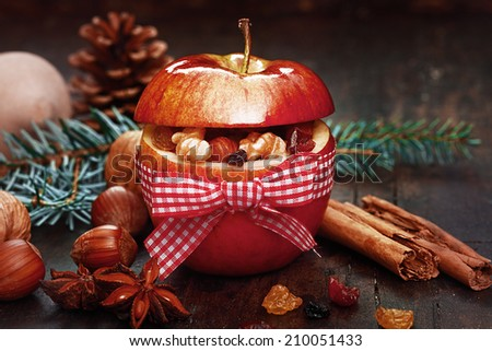Christmas Spices in Red Apple with Ribbon, Cinnamon Sticks, anise, and Nuts on Side. - stock photo
