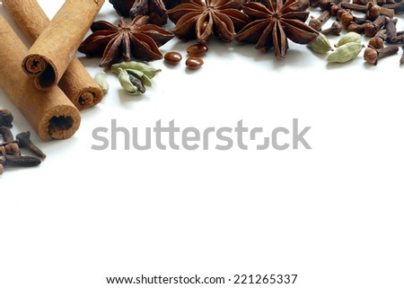 Christmas spices, tea or baking ingredients for winter, cinnamon, cardamom, cloves, anise stars, close up on white background with copy space - stock photo