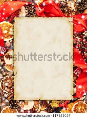 Christmas spices with dry orange and apple slices in frame with blank old paper - stock photo