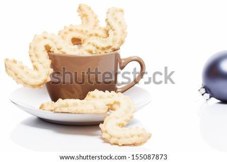 christmas spritz cookies in a brown coffee cup on white background - stock photo