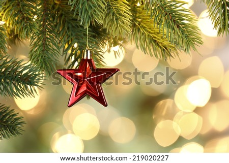 Christmas star and lights hanging on fence at snowy night - stock photo
