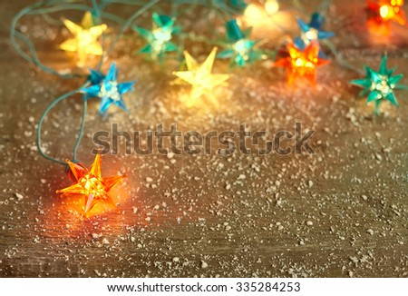 Christmas star lights frame on wooden background with copy space. Decorative garland - stock photo