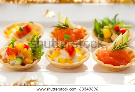 Christmas starter platter with appetizers.Tartlets with three different fillings(vegetable salad,crab salad and smoked salmon with apple) - stock photo