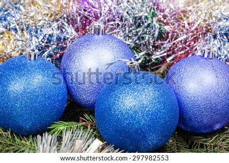 Christmas still life - four blue and violet Christmas balls, colorful tinsel on Xmas tree background - stock photo