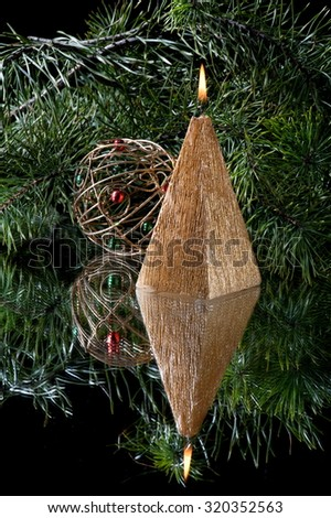 Christmas still-life from candles in the shape of a pyramid and the Christmas decorations standing in the mirror, on the background of fir branches - stock photo