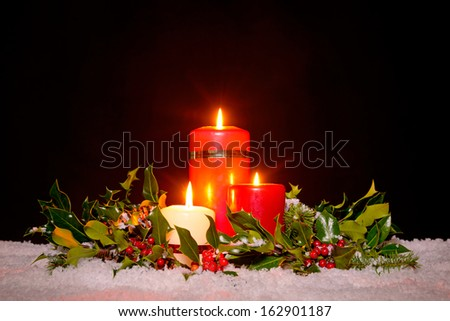 Christmas still life of three candles on snow surrounded by a fresh green holly, ivy and spruce garland against a black background. - stock photo