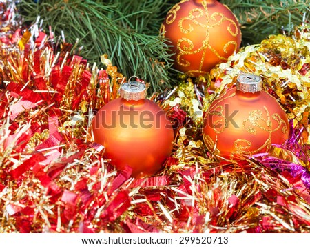 Christmas still life - three orange and yellow Christmas balls, red tinsel on green Xmas tree background - stock photo