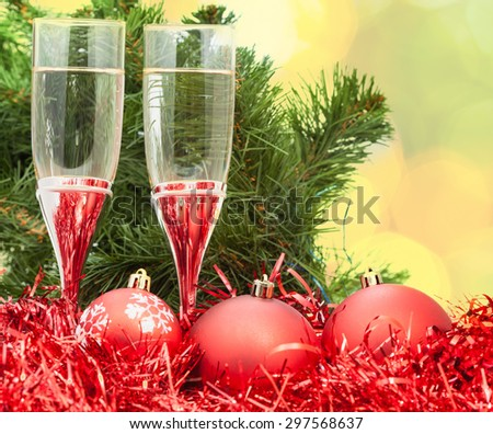 Christmas still life - Two glasses of champagne with red Xmas decorations on Christmas tree and blurred yellow background - stock photo