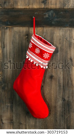 Christmas stocking. Red sock with snowflakes for Santa gifts hanging over rustic wooden background. Winter holidays decoration - stock photo