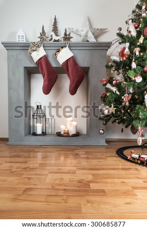 Christmas stockings hanging from a candle fireplace, christmas tree on the right. copy space on the floor below - stock photo