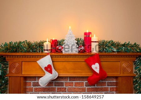 Christmas stockings hanging over a fireplace with candles on the mantlepiece - stock photo
