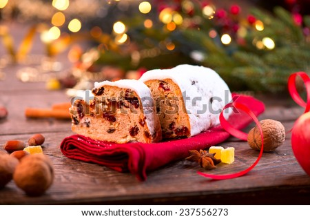 Christmas Stollen. Traditional Sweet Fruit Loaf with Icing Sugar. Xmas holiday table setting, decorated with garlands, baubles, wallnuts, hazelnuts, cinnamon sticks. Warm colors toned.  - stock photo
