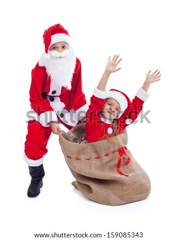Christmas surprise- kids dressed as santas having fun with large bag, isolated - stock photo