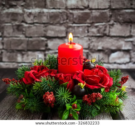 Christmas table decoration with burning red candle. - stock photo