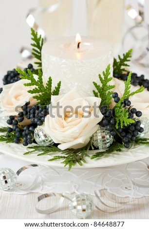 Christmas table decoration with roses,winter berries and candle - stock photo