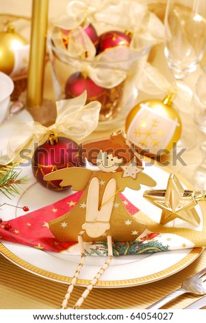 christmas table decoration with wooden angel on plate in golden and white colors - stock photo