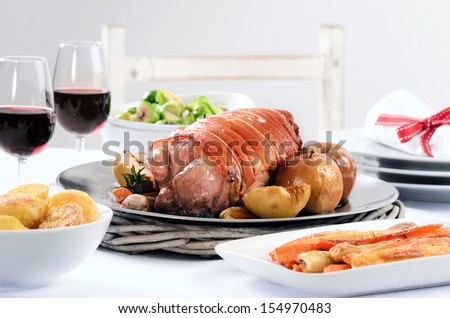 Christmas table meal with pork roast, potatoes, honey glazed carrots, brussels sprouts sides and wine on a festive table  - stock photo