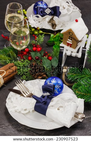 Christmas table place setting. Christmas decorations on a place setting with wine glasses and edible mini gingerbread house.  Macro, selective focus - stock photo