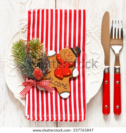 Christmas table place setting. Elegant empty plate, cutlery, candy cane napkin and funny gingerbread men. - stock photo