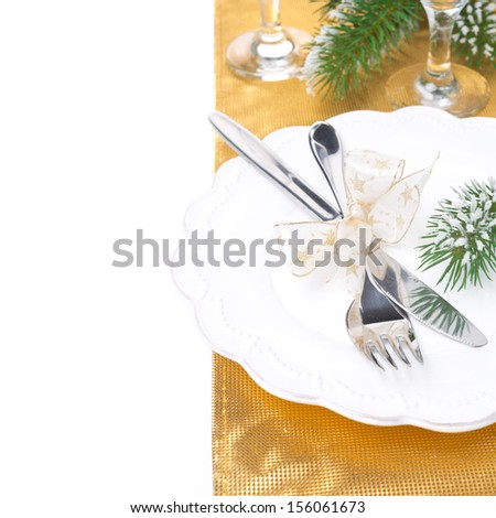 Christmas table place setting in golden tones, isolated on white - stock photo