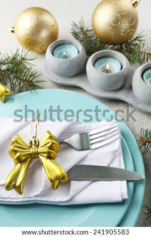 Christmas table setting in blue, golden and whitec olors on grey tablecloth background - stock photo