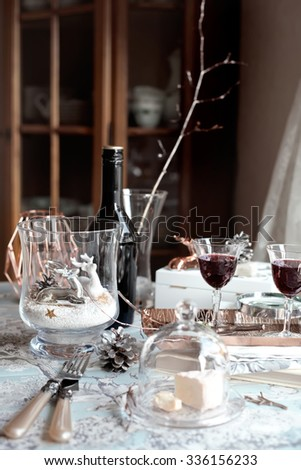 Christmas table setting with decorations and glasses of port wine/sherry and cheese. Retro/classic/imperial style accessories. Natural light photo. Shallow focus. Toned photo. - stock photo