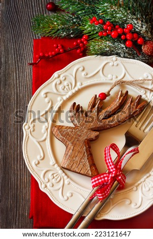 Christmas table setting with decorative wooden deer. - stock photo